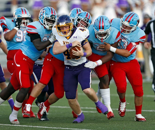 Lubbock Monterey defenders tackle Wylie's Logan Hollenbeck (44) during the game against Abilene Wylie, Thursday, Sept. 5, 2019, at Lowrey Field in Lubbock.