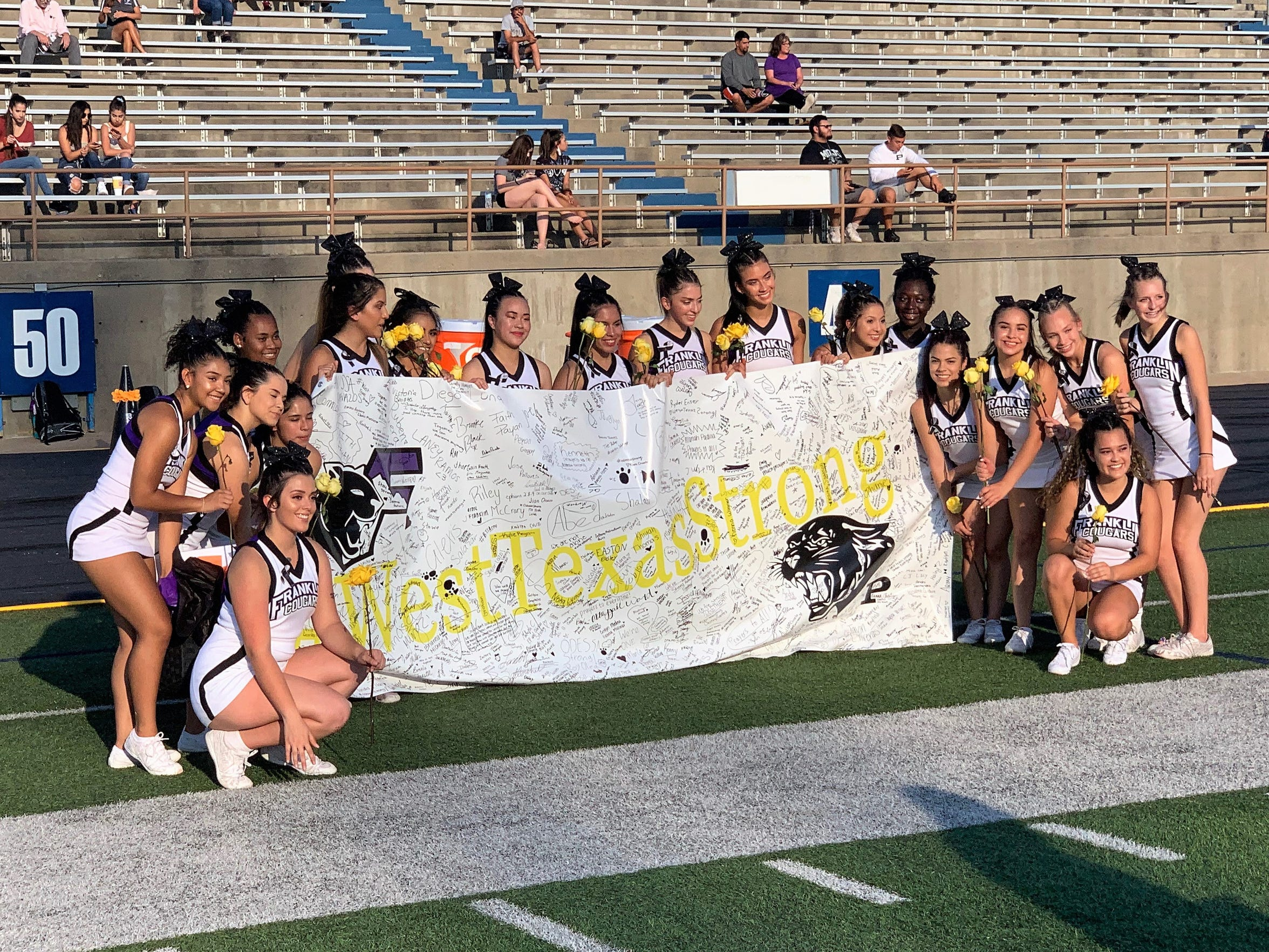 El Paso Franklin cheerleaders pose with the #WestTexasStrong banner and yellow roses presented by the Odessa Permian student body at Ratliff Stadium on Thursday.