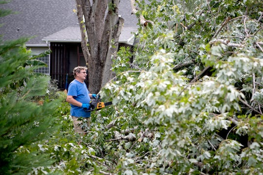 Drew Roper uses a chainsaw to start to clean up fallen trees and limbs in his yard in Myrtle Grove, North Carolina following Hurricane Dorian on Sept. 6, 2019.
