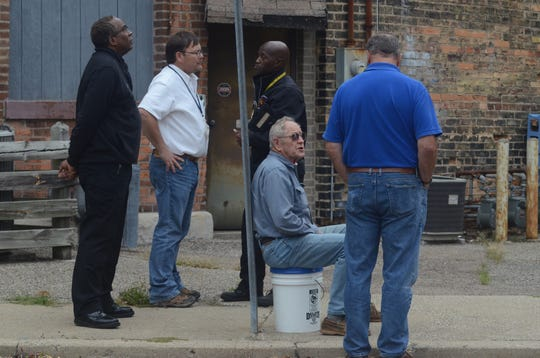 Bryant Debolt, seated, speaks with Ed Harris from the City of Battle Creek while Fire Chief Brian Sturdivant, from left, Richard Bolek, inspections supervisor, and Quincy Jones, fire marshal, discuss the building condition.
