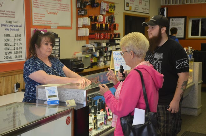 Keri Bruneel shows MIkel Yingling and Barbara Latshaw one of the products at BC Vaping Ape.