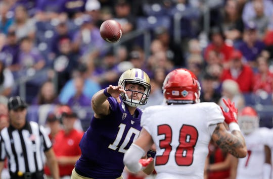 Washington quarterback Jacob Eason (10) throws a touchdown pass as Eastern Washington's Joe Lang defends in the first half of an NCAA college football game Saturday, Aug. 31, 2019, in Seattle. (AP Photo/Elaine Thompson)