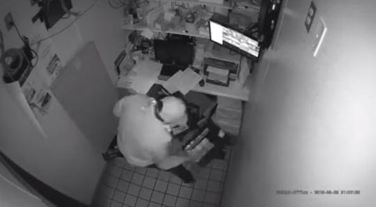 A screen grab from Dunkin' surveillance video shows a person taking a cash register till from the office.