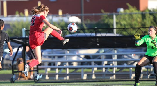 Lakota West player Kailyn Dudukovich  (13) scores a goal past Lakota East goalie Rylee Oldfield (0) during their soccer game, Thursday, Sept. 5, 2019.