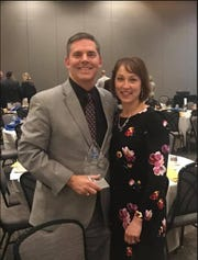 Tom Burton, Princeton City Schools superintendent, joins his wife, Franca, after accepting the 2018 Business Person of the Year award at the Champions of Commerce Celebration Feb. 21.