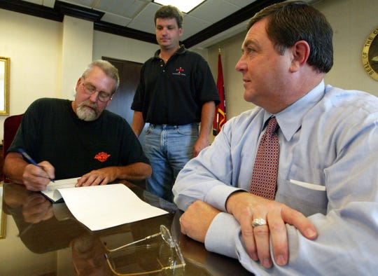 Bikers Who Care President Bill Langford, left, signs a deed for city land as Jamie Milam, center, and Mayor Don Trotter watch in July 2003. The club was planning to build a park for children with disabilities on South Second Street, near Crossland Avenue.