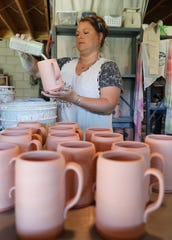 Rachel Jane Hall pours glaze into a mug before firing it at her studio, Hillbippie Clay Company, in Coshocton.