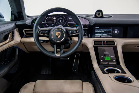 The interior of the Porsche Taycan electric car is nearly devoid of buttons and knobs.