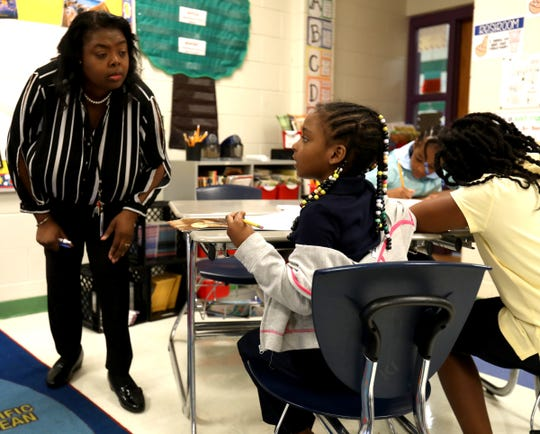 Third grade teacher Michelle Ballard listens to one of her students, Aaliyah Thompkins look over a problem on the smart board and give her an answer during class at the Charles Wright Academy of Arts and Science in Detroit, Michigan on Friday, Sept. 6, 2019.