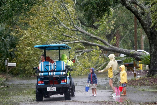Isle of Palms residents look at a downed tree on Hartnett Blvd. during Hurricane Dorian at the Isle of Palms, S.C., Thursday, Sept. 5, 2019, in Charleston, S.C.