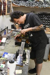 Guitar maker Gabriel Currie works on an Echopark guitar.