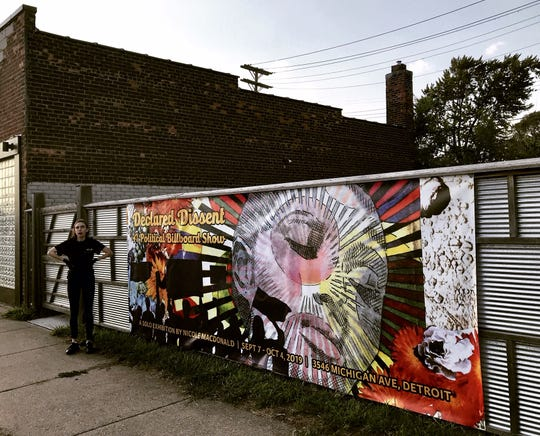 Nicole Macdonald with the billboard poster she painted for her Holding House show.