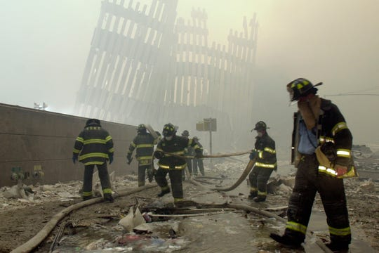 Firefighters work beneath the destroyed mullions, the vertical struts which once faced the outer walls of the World Trade Center towers, after a terrorist attack on the twin towers in New York on Sept. 11, 2001.