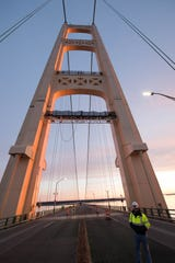 Members of Seaway Painting raise a painting platform on the north tower of the Mackinac Bridge
