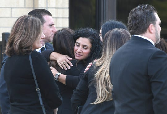 Friends and family of Jimmy Aldaoud, a refugee who died after he was deported to Iraq, embrace before his funeral service at The Mother of God Chaldean Catholic Church in Southfield on Friday.