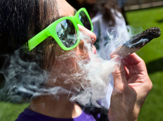 """In this Friday, March 22, 2019 file photo, a participant takes a very smoky puff from a marijuana cigarette during a meet and greet at """"Tommy Chong's Live, Love, and Smoke Tour hosted by GreenTours in the Woodland Hills section of Los Angeles."""