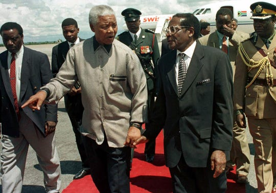 Former South African president Nelson Mandela, left, walks with Zimbabwean President Robert Mugabe in Harare. Mugabe, the longtime leader of Zimbabwe who was forced to resign in 2017 after a military takeover, has died at 95.