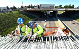 Ben Hildebrand, left, of Romulus, and foreman Michael Irish, of Birch Run, make repairs in August 2019 to the I-94 bridge over Middlebelt.