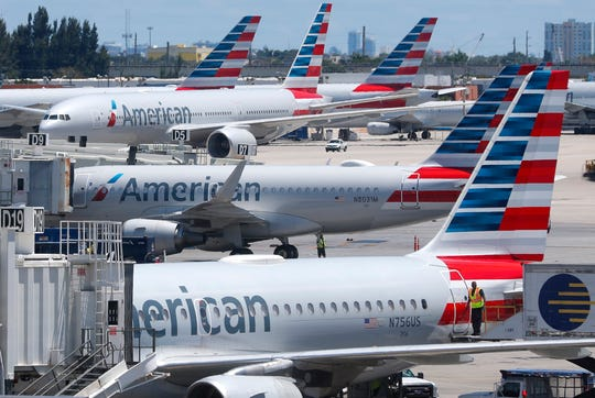 In this April 24, 2019, photo, American Airlines aircraft are shown parked at their gates at Miami International Airport in Miami.