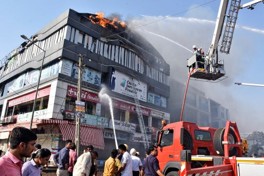 FILE - In this Friday, May 24, 2019 file photo, firefighters spray water on a burning building in Surat, in the western Indian state of Gujarat. On Friday, Sept. 6, 2019, The Associated Press reported on altered videos from this event, circulating online incorrectly identified as a South African mall ablaze with people leaping from the building amid civil unrest in the country. In early September 2019, there has been a rise in looting and arson attacks against foreign-owned businesses in Johannesburg and South Africa's capital, Pretoria. (AP Photo/Sarju Parekh)