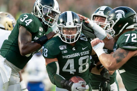 Michigan State defensive end Kenny Willekes celebrates with teammates after recovering a fumble for a TD in the second quarter.