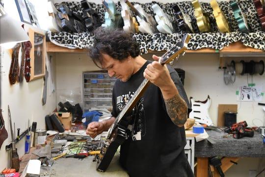 Guitar maker Gabriel Currie works on an Echopark guitar.