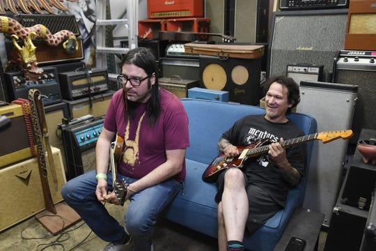 Friend and customer Chris Koltay, left, and Gabriel Currie test guitars in the Echopark amp room.