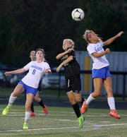 Katie Grottenthaler (center) goes up for a ball in the air along with Horseheads' Chloe Eberhard (8) and Leah Karabaich (1) in girls soccer Sept. 5, 2019 at Corning Memorial Stadium.