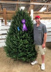 Chris Duffy of Whispering Pines Tree Farm in Oconto stands with his winning tree at the Wisconsin Christmas Tree Association state contest on Aug. 16 in Waldo, Wis. The win means Whispering Pines will provide a tree for the Governor's residence this year.