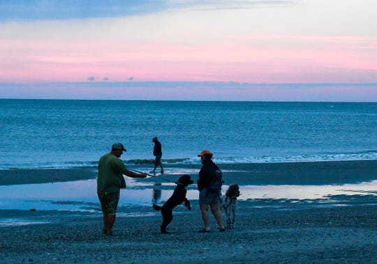 JR and Dana Hammond walk their poodles and gather seashells on the beach near the Boardwalk after Hurricane Dorian blew through Myrtle Beach, South Carolina and a sunrise to start Friday, Sept. 6, 2019.