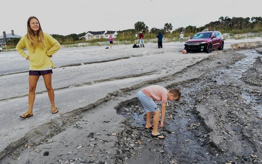 Anna King and her son Kaden King pick up shells near a stranded Jeep car in Myrtle Beach, South Carolina Friday, Sept. 6, 2019.