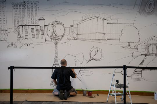Adam Schrimmer works on a mural inside Haywood Mall Friday, Sept 6, 2019. The mural comprises scenes and figures from Greenville.