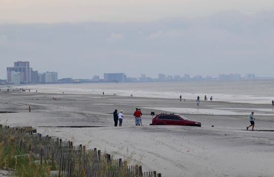 The abandoned Jeep remained on the Myrtle Beach shore Friday morning.