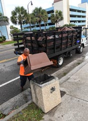Terence Powell puts a lid back on a North Ocean Boulevard garbage can in Myrtle Beach, South Carolina Friday, Sept. 6, 2019. Powell said the city took them off before Hurricane Dorian came so they would not blow off.