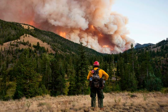 Tatanka Hot Shot Kurt Bassett, of the Black Hills-area in South Dakota, watches the Fishhawk Fire barrel toward Kitty Creek drainage in Shoshone National Forest 40 miles west of Cody, Wyo. on Wednesday, Sept. 4, 2019. (Rebecca Noble/The Billings Gazette via AP)