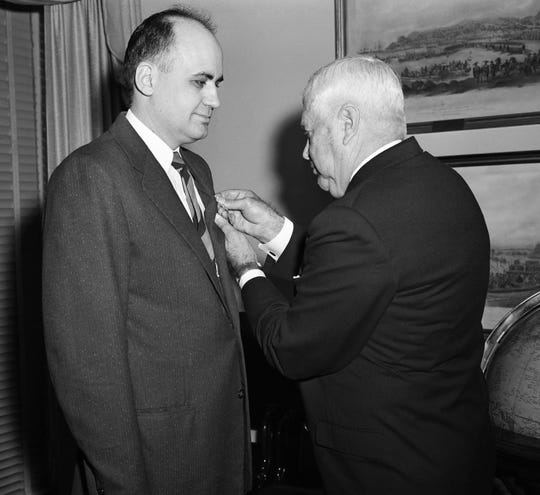 File - In this April 18, 1957, file photo, Dr. Maurice Hilleman, left, Walter Reed army medical center, receives distinguished civilian service award from Secretary of Defense Wilson at the Pentagon. Montana State University is celebrating what would have been the 100th birthday of the scientist credited with saving millions of lives through the development of vaccines against measles, mumps and other diseases. Maurice Hilleman was born in Miles City in 1919, graduated from MSU in 1941 and died in 2005. The first Hilleman scholars are set to graduate from MSU this year. (AP Photo/File)