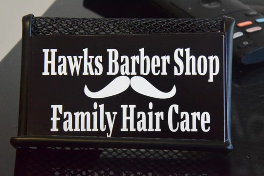 """Owner Kim Reed makes sure each client takes a card at Hawks Barber Shop and Family Hair Care Wednesday Sept. 3. """"I want people to come back time after time. It's all about client loyalty and quality haircuts. I love to see a familiar face coming back."""""""
