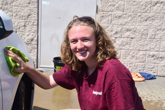 Coloette Lucas, 15, sponges grime off the fender of a dirty car at a fundraiser sponsored by Karns High School Choir. 8/31/19