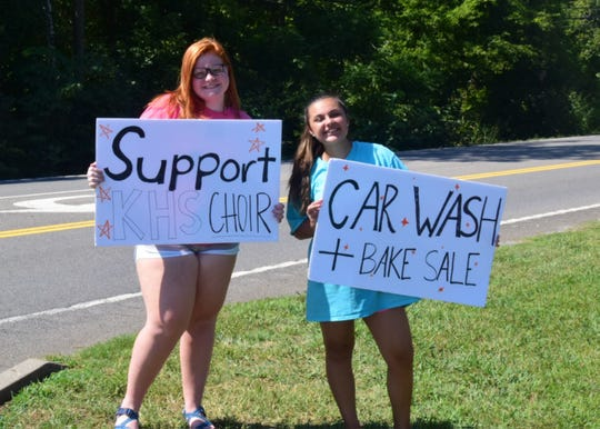 Addison Garrett, 14, and Jasmine Aleman, 14, draw passersby to a car wash fundraiser sponsored by Karns High School Choir and held at Advance Auto Parts on Saturday, Aug. 31. 2019