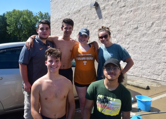 Sam Pinkston, 16; Demarckus Garner, 16; (back) Joshua Berlin, 17, Caleb Foster, 16, Emma Greene, 17, and Meredith McNeeley, 16, at a car wash fundraiser sponsored by Karns High School Choir and held at Advance Auto Parts on Saturday, Aug. 31.