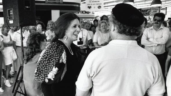 June Carter Cash chats with mandolin player Red Rector during her appearance at Kroger on Chapman Highway, June, 1989.