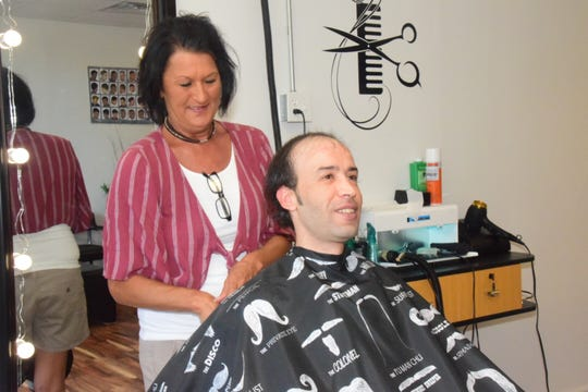 Joseph Merybet, owner of Bella Roma Pizza, prepares for a haircut using Kim Reed's special vacuum clippers at Hawks Barber Shop and Family Hair Care Wednesday Sept. 3.