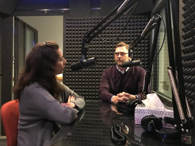 Michigan History Center Engagement Specialist Sara Gross, left, and Michigan State Archivist Mark Harvey talk to each other in a sound booth at the History Center. Michigan residents can share their stories through a project between the Michigan History Center and StoryCorps.