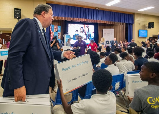 Senior Executive Vice President at Comcast, David L. Cohen, hands out laptops to students at Cummings School, a K-8 school in the Soulsville neighborhood Friday, September 6, 2019.