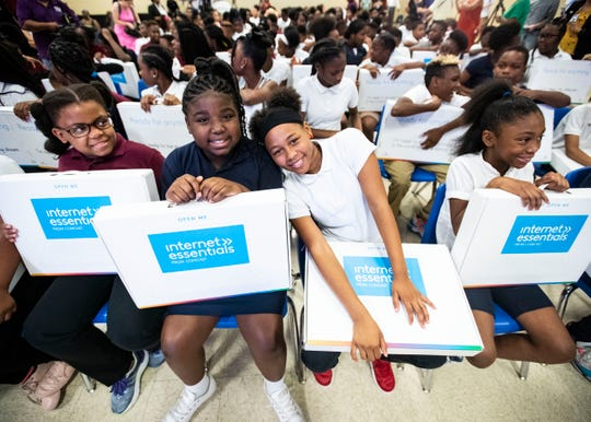 Cummings K-8 School students cheerfully pose with their brand new laptops from Comcast Internet Essentials program a during the eligibility expansion announcement Friday, September 6, 2019.