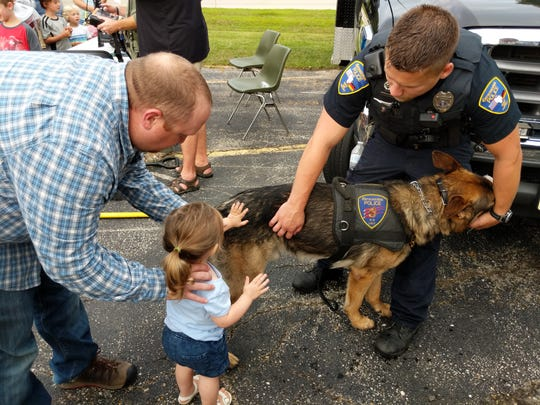 Lainie Stevens pets K-9 Hatto at the Germantown Night Out in 2018. Lainie is pictured with her father, Michael, and Hatto's handler, Officer Darren von Bereghy.
