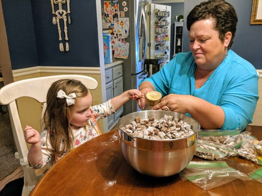 Lainie and her grandmother, Sue Moroski, pour homemade puppy chow into bags. Lainie sold puppy chow and lemonade to benefit the Germantown Police Department's K9 unit.