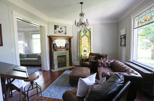 The living room has a fireplace that once burned coal and a stained glass window from a church.