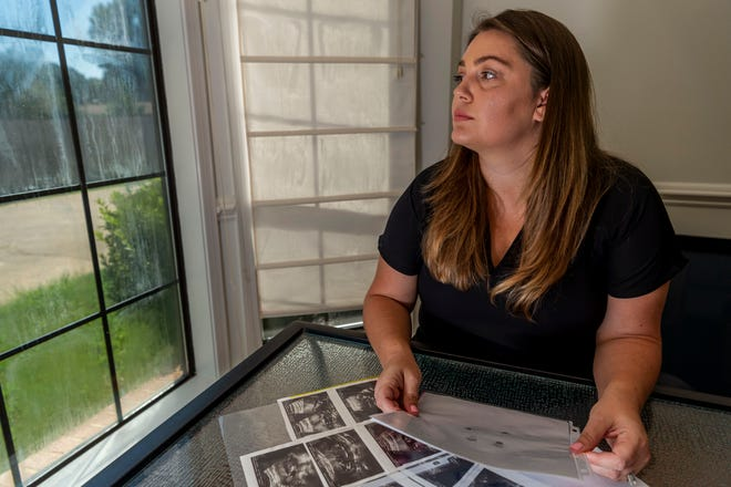 """Hevan Lunsford poses for a photo with her son's ultrasounds and footprints and handprints of her son in Prattville. """"I felt the only way to guarantee that he would not have any suffering was to go through with the abortion,"""" she said of that painful decision nearly three years ago."""