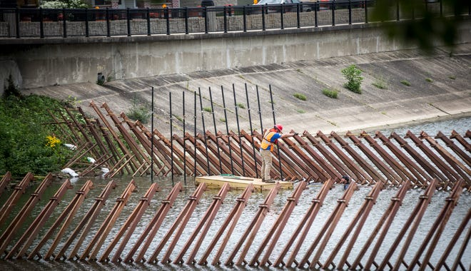 Construction crews work on installing a temporary dam near the High Street bridge near Muncie's downtown for a sewer maintenance project. The project is expected to take 4-5 weeks.